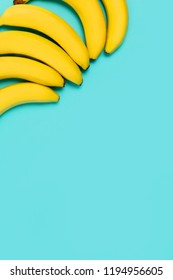 Beautiful yellow bananas on blue colorful background with copy space for text