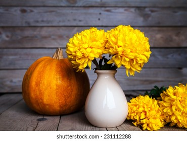 Beautiful yellow chrysanthemum on the old wooden background. Pottery vase with flowers. Ripe pumpkin