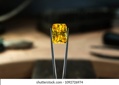 Beautiful yellow diamond stone in tongs. Craft jewelery making with professional tools in jeweller studio. Macro shot. A handmade jeweler process, manufacture of jewelry.
