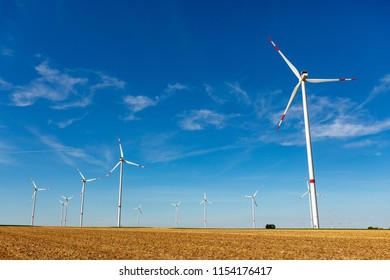 Beautiful yellow farmland landscape with white wind turbines with red stripes generating electricity on a bright blue little cloudy sky.