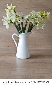 Beautiful yellow / green daffodil in a jug on a wooden background