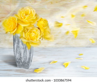 Beautiful yellow roses in a stone vase against a soft blue and yellow wooden background with blowing petals