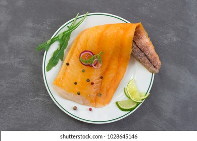 beautiful yellow smoked haddock fish fillet on a plate with a branch of fresh arugula, lime and pink berry on slate background