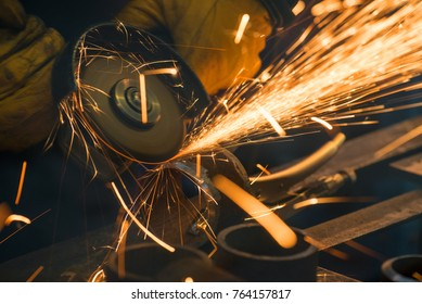Beautiful yellow sparks from the rotation and cutting of metal by hand grinder as background