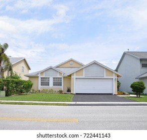 Beautiful Yellow Suburban Home Snout Style blue sky clouds Florida USA
