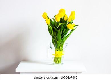 Beautiful yellow tulips flowers in white interior closeup