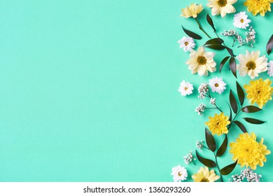 Beautiful yellow and white flowers composition on blue background, top view, flat lay