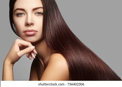 Beautiful yong woman with long straight brown hair. Sexy fashion model with smooth gloss hairstyle, keratin treatment