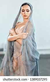 Beautiful young actress or dancer in a stage costume of a fisherman s bride, a long robe made of beige fabric much alike fishnets. Female head is covered with grey veil made from the same material.