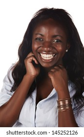 Beautiful young adult African woman with long dark hair against a white background wearing a white shirt