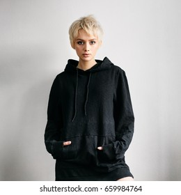 Beautiful young adult blonde woman in black hoodie on white wall