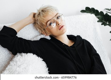 Beautiful young adult blonde woman in black hoodie on the white sofa