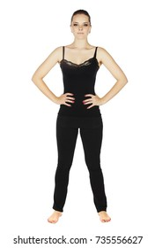 Beautiful young adult caucasian woman with dark hair on a light, standing on a white background with a black top and yoga pants