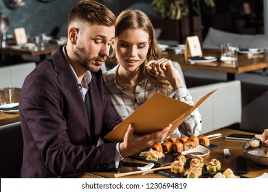 Beautiful young adult couple looking in menu to order dinner in restaurant