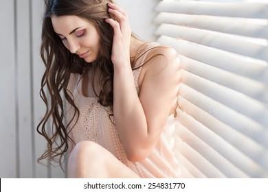 Beautiful  young adult sensuality brunette woman sitting on the window. Beautiful peach morning light