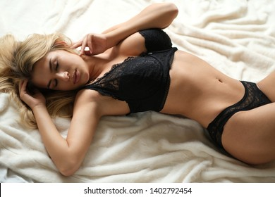 Beautiful young adult sexy woman lying in black lingerie.