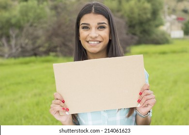 Beautiful young adult smiling woman holding cardboard in park