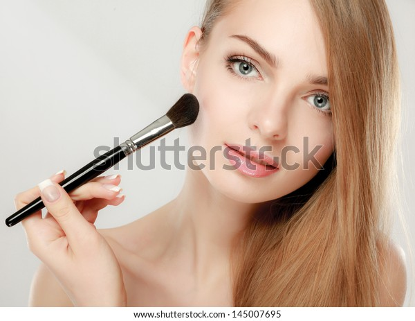 Beautiful young adult woman applying cosmetic paint brush