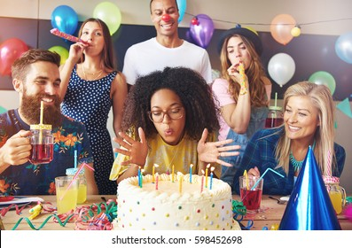 Beautiful young adult woman blowing out candles on her cake at birthday party surrounded by celebrating friends