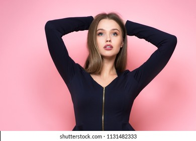 Beautiful young adult woman looking up holding hands on her head isolated on pink background