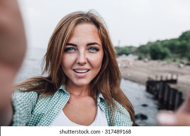 beautiful young adult woman taking picture of herself, selfie.