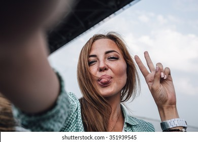 beautiful young adult woman taking picture of herself and shows tongue, selfie.