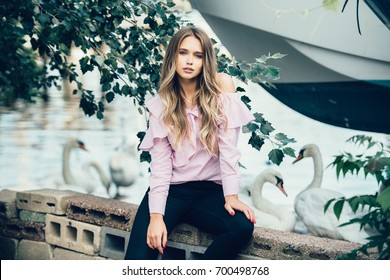 Beautiful young adult woman wearing fashionable summer outfit sitting near lake with swans and green trees. Fashion model photo.
