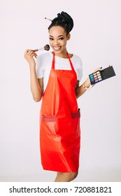 Beautiful young African American beautician woman holding set of make up brushes.