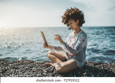 Beautiful young African American girl with curly afro hair is sitting on the sea pebble beach and listing photos on her digital tablet on warm and sunny summer day with waterscape in the background
