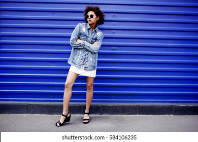 Beautiful young African American hipster woman with afro in a dress. Lifestyle, outdoors