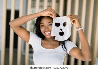 Beautiful young African American lady in white t-shirt, enjoying her beauty procedures at home, going to apply a white face sheet mask on face. Spa procedures at home