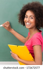 Beautiful young African American student with an afro hairstyle and vivacious smile holding a file and writing on a blackboard