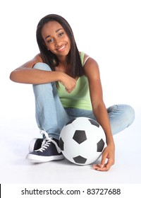 Beautiful young African American teenage school girl soccer player, sitting on the floor with a football. Girl wearing blue jeans and casual vest and has a big happy smile.
