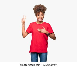 Beautiful young african american woman over isolated background Swearing with hand on chest and fingers, making a loyalty promise oath