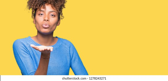 Beautiful young african american woman over isolated background looking at the camera blowing a kiss with hand on air being lovely and sexy. Love expression.