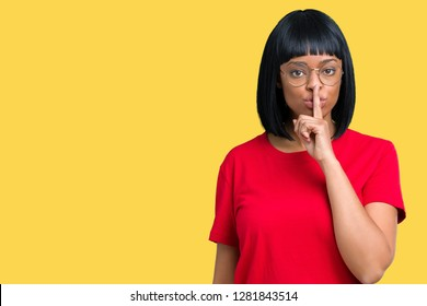 Beautiful young african american woman wearing glasses over isolated background asking to be quiet with finger on lips. Silence and secret concept.