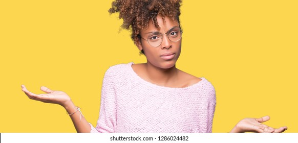 Beautiful young african american woman wearing glasses over isolated background clueless and confused expression with arms and hands raised. Doubt concept.