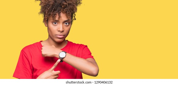 Beautiful young african american woman over isolated background In hurry pointing to watch time, impatience, upset and angry for deadline delay