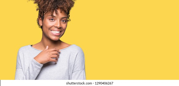 Beautiful young african american woman over isolated background looking confident at the camera with smile with crossed arms and hand raised on chin. Thinking positive.