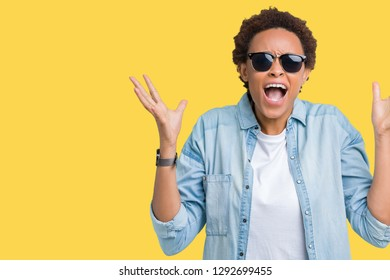 Beautiful young african american woman wearing sunglasses over isolated background celebrating crazy and amazed for success with arms raised and open eyes screaming excited. Winner concept
