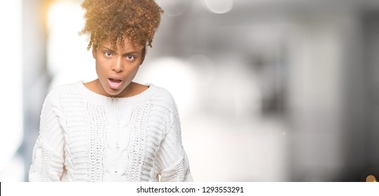 Beautiful young african american woman wearing winter sweater over isolated background In shock face, looking skeptical and sarcastic, surprised with open mouth