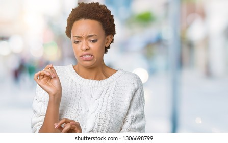 Beautiful young african american woman wearing sweater over isolated background disgusted expression, displeased and fearful doing disgust face because aversion reaction. With hands raised. Annoying