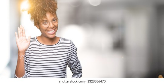 Beautiful young african american woman wearing glasses over isolated background Waiving saying hello happy and smiling, friendly welcome gesture