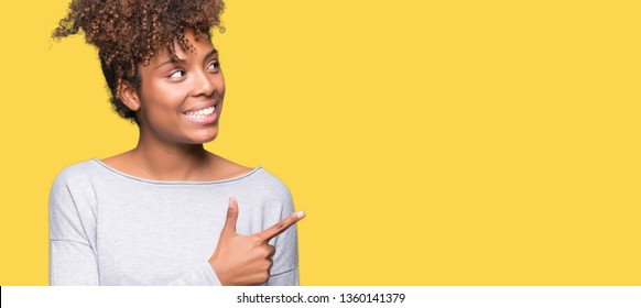 Beautiful young african american woman over isolated background cheerful with a smile of face pointing with hand and finger up to the side with happy and natural expression on face