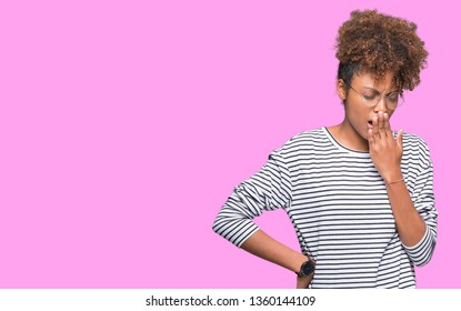 Beautiful young african american woman wearing glasses over isolated background bored yawning tired covering mouth with hand. Restless and sleepiness.