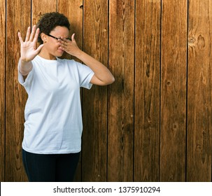 Beautiful young african american woman wearing glasses over isolated background covering eyes with hands and doing stop gesture with sad and fear expression. Embarrassed and negative concept.