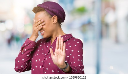 Beautiful young african american woman wearing head scarf over isolated background covering eyes with hands and doing stop gesture with sad and fear expression. Embarrassed and negative concept.