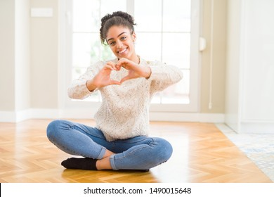 Beautiful young african american woman with afro hair sitting on the floor smiling in love showing heart symbol and shape with hands. Romantic concept.