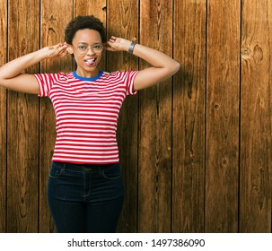 Beautiful young african american woman wearing glasses over isolated background Smiling pulling ears with fingers, funny gesture. Audition problem