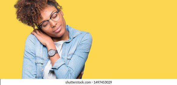 Beautiful young african american woman wearing glasses over isolated background Hugging oneself happy and positive, smiling confident. Self love and self care
